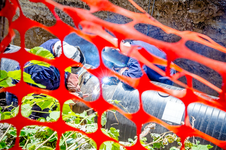 Welders are in trench they arc welding pipeline. Confined space with orange, plastic, safety net