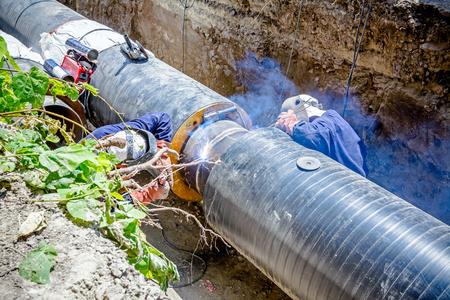 manpower: Team of welders is in trench working hard to install a new pipeline. Arc welding pipes
