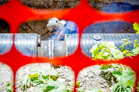 manpower: Welder is in trench arc welding pipeline. Confined space with orange, plastic, safety net