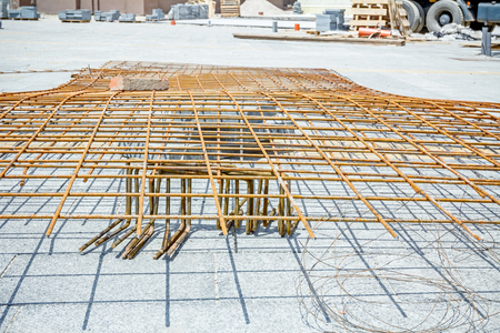 wire mesh: Spikes of rebar grid, reinforcing mesh, steel bars stacked for construction. Stock Photo