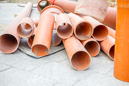 distributed: Sewer pipes waiting to be placed into the ditch at construction site.