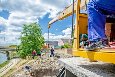 끈이있는 크레인 후크는 먼지가 많은 땅 위의 거대한 긴 파이프를 끌고 있습니다. 스톡 콘텐츠