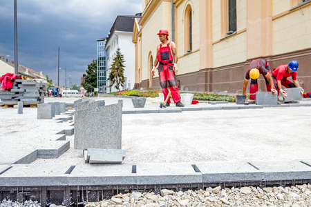 Zrenjanin, Vojvodina, Serbia - June 19, 2015: Team of masons is fitting flagstone, they making footpath paving large street.