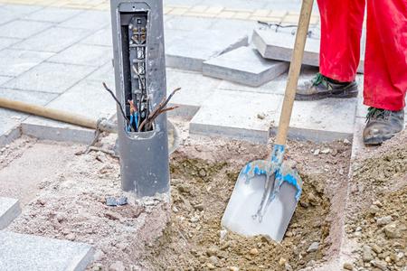 労働者は余分な材料を除去することによって電気金属街灯の基地周辺のシャベルと砂利を平準化します。 写真素材