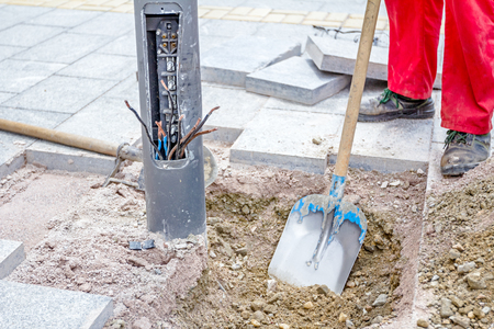 Worker is leveling gravel with shovel around the base of the electric metal lamppost by removing excess material. Stock Photo
