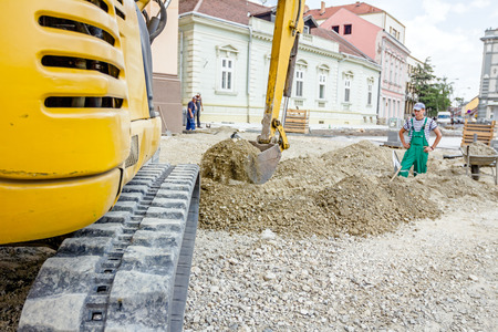 Small excavator is excavating soil at construction site, project in progress.