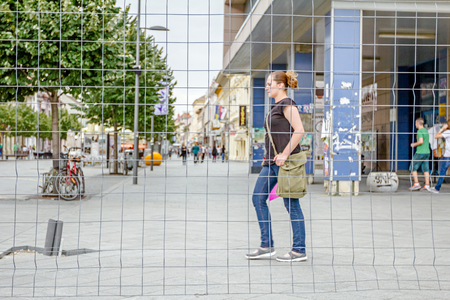 Zrenjanin, Vojvodina, Serbia - June 19, 2015: View through a fence wire with quadratic shape on the business people passing by in the city street.