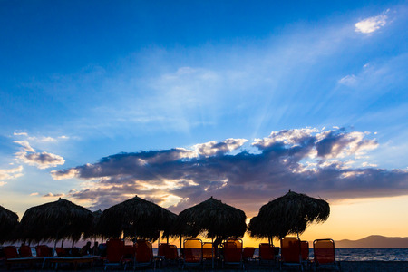 Silhouetted shot of the beach with sunshades made of straw, umbrellas and deckchairs for a perfect holiday. Stock Photo