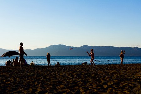 Silhouetted shot of father and daughter playing with flying disk at beach, they are throwing frisbee. Stock Photo