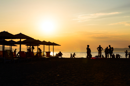 Silhouetted shot of sunset on the beach with people and sunshades, umbrellas for a perfect holiday.