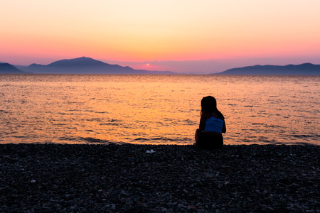 Silhouette view of young girl who is alone and thinking away at the beach next to the coastline with sunset over sea.