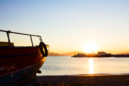 Silhouetted scenic view of old boat dry docked in a beautiful sunset at the beach, coastline.