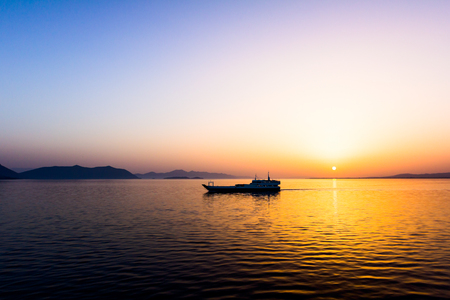 manage transportation: View on morning horizon with a ferry boat that is crossing over calm sea. Stock Photo