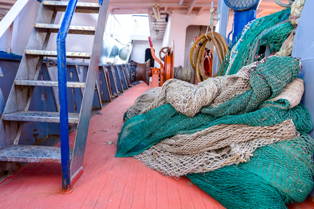 Pile of commercial fishing net, equipment for angling at open sea on wide ships deck.