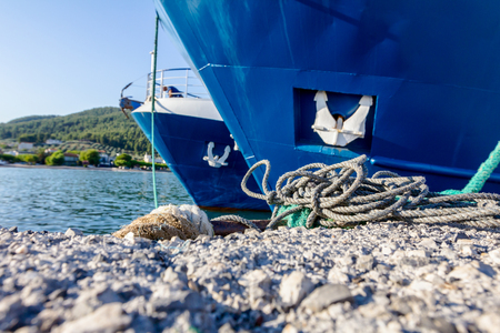 commercial fishing: Docked two large fishing ships tied with rope to a moor at the local port.