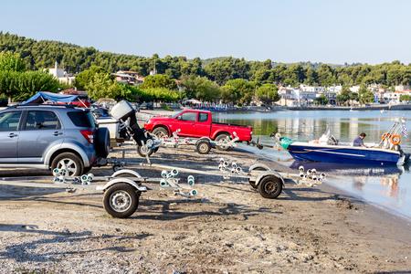 Několik automobilů je zaparkováno na pláži s přívěsy pro přepravní čluny.