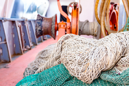 Heap of commercial fishing net and extraction mechanism is in background.