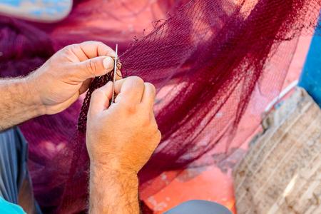釣りのためにネットを修復漁師手でスレッドは針します。