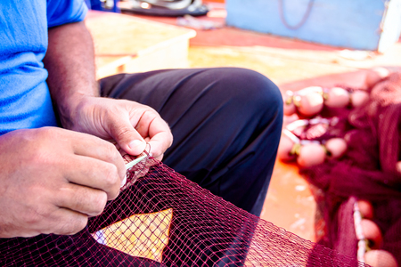 Needle with thread in fisherman hands repairing net for angling.