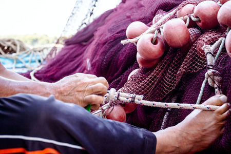 Fisherman is helping himself using a leg to tie up rope with needle in hands repairing net for angling. Stock Photo