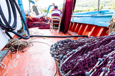Pile of commercial fishing net, equipment for angling at open sea. Stock Photo