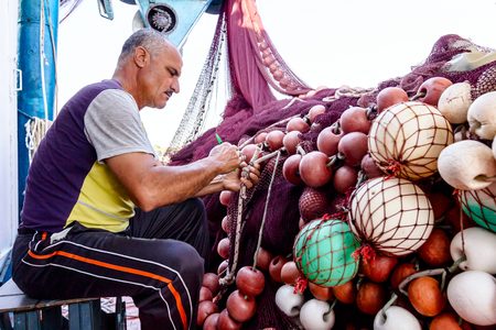 Pefki, Island Evia, Greece - 10, July 2017: Needle with thread in fisherman hands repairing net for angling.