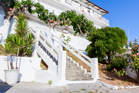 Luxury house with colored stairs and green vegetation is placed in idyllic and peaceful place.