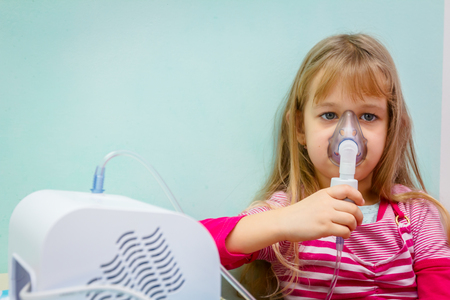 Child with asthmatic problems is take inhalation with mask on her face.