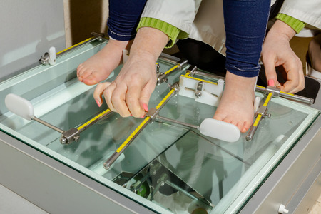 Doctor orthopedist is measuring childs foot with adjustable metal rulers.