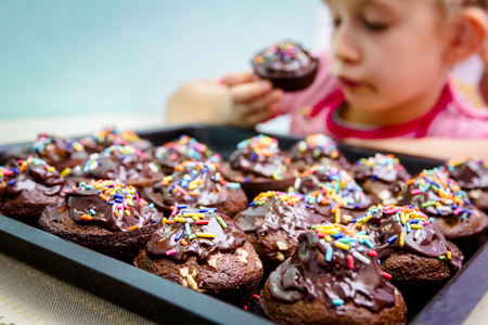 Little cute girl with chocolate on face and hands is eating a decorated muffin.