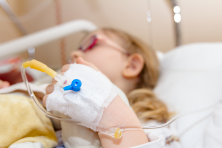 Little girl is receiving medication through intravenous fluid therapy in hospital bed, focus on drip. Stock Photo