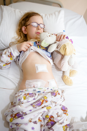 Little girl has medical patch on her belly and catheter tube after surgical operation of appendix.
