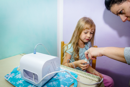 Woman is preparing inhalation treatment for child with asthmatic problems.