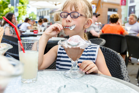 Little cute girl with glasses and carefree face expression is eating ice cream at table in pastry shop in summertime. 免版税图像