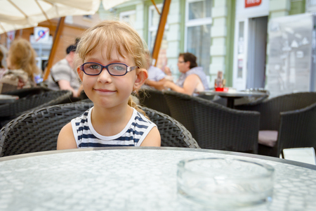 Portrait of sweet little girl with glasses and carefree expression on her face at pastry shop.