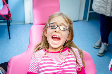 Frightened sweet little girl with open mouth is at dentist office, dental care.