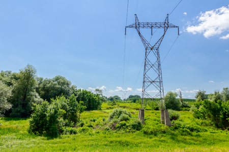Tall power line going trough landscape, blue clear sky is above.