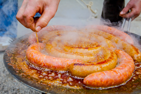 Hand with wooden toothpick is making small holes in simmering sausages on a black barbecue grill.  Stockfoto