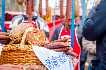 Selling cured meat and sausages, salami for sale at outdoor flea market.