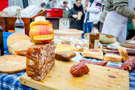 Headcheese and smoked sausage on a wooden chopping board at outdoor kitchen, people in background are preparing meat for handmade sausages.