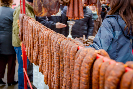 Bunch of lined cured sausages hang for sale at outdoor flea market. Stock Photo