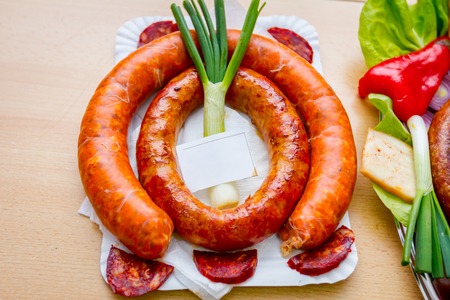 Roasted sausage with young onion is arranged with green onion in traditional style.