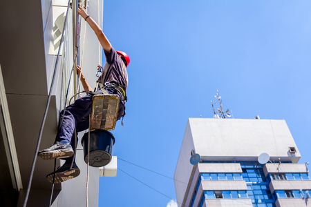 View from below on young man, industrial climber at work, he washing building facade. Reklamní fotografie