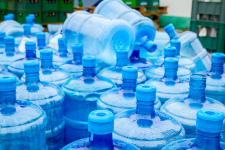 Big empty plastic water bottles for the cooler are stacked at outdoor warehouse.
