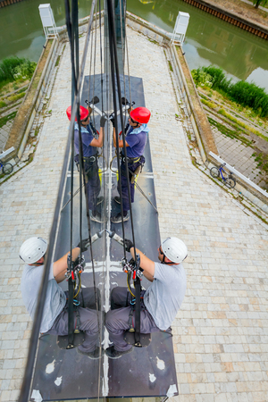 Industrial climbers are applying silicone to rubber juncture among building's glass facade. Stock Photo