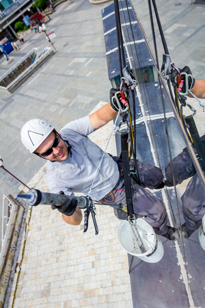 Industrial climber is applying silicone to rubber juncture among building glass facade.