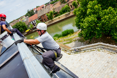 Industrial climber, alpinist, is passes over roof edge. He is climb down to wash building. Stock Photo
