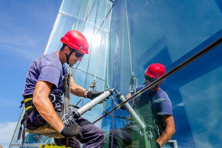 Escalador industrial está aplicando silicona a la unión de caucho entre la fachada de vidrio del edificio.