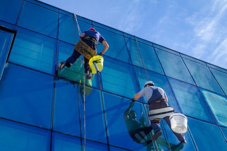 Industrial climbers are applying silicone to rubber juncture among buildings glass facade.