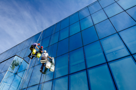 Industrial climbers are applying silicone to rubber juncture among building's glass facade. Imagens